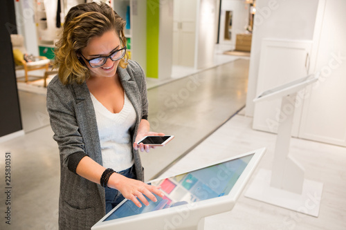 Woman uses the self-service kiosk in the store Wallpaper Mural