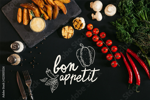 Plakaty do jadalni top-view-of-tasty-baked-potatoes-with-sauce-spices-and-vegetables-on-black-with-bon-appetit-lettering