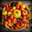 Wooden bowl with fresh vine ripened heirloom tomatoes from farmers market