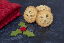 Three Mince Pies On A Dark Background With Christmas Decoration