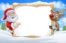 Santa Claus And Reindeer Christmas Cartoon Characters In A Winter Scene Pointing At A Sign