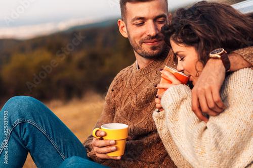 Fényképezés  Beautiful young couple enjoying picnic time on the sunset