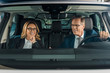 smiling business couple sitting in new car for test drive