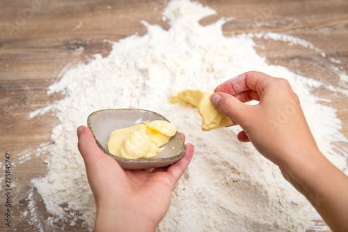 Frau gibt Butter in Mehl auf dem Tisch, Mürbeteig und Backen