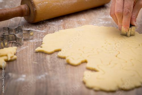 Weihnachtsbäckerei, Frau beim Plätzchen ausstechen, Teigrolle im Hintergrund