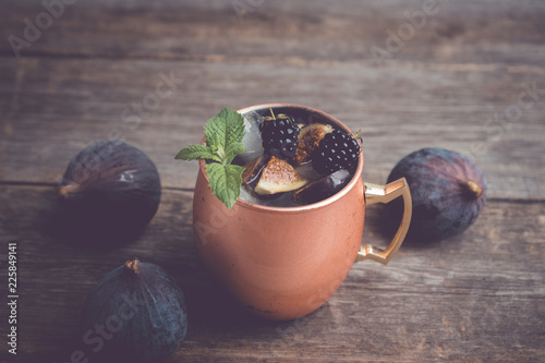 Moscow mule cocktail with figs in copper mug on the wooden background. Selective focus. Shallow depth of field.
