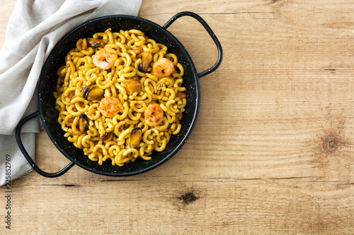 Traditional Spanish fideua. Noodle paella on wooden table. Top view. Copyspace