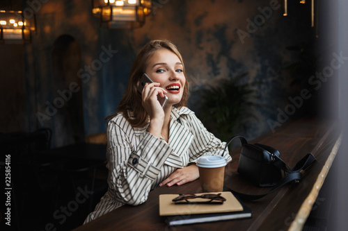 Photo  Young cheerful woman in striped trench coat talking on cellphone happily looking