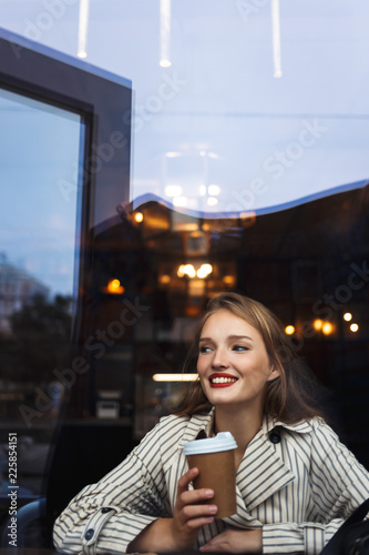 Fotografia  Young beautiful smiling woman in striped trench coat holding cup to go in hand h