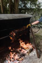 Man Rotating Hog Roast Spit In Garden, Cropped