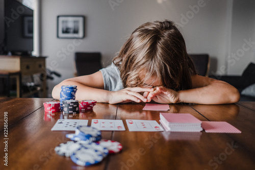 Girl playing cards at table with head down