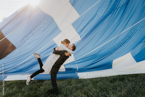 Newly engaged couple kissing, hot air balloon in background