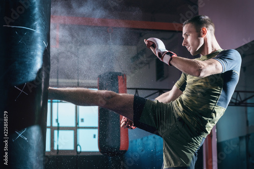 The young man workout a kick on the punching bag in gym. Canvas Print