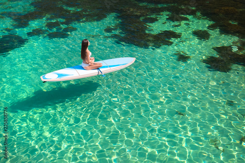 Young Attractive Woman Meditating On The Sup Board In The