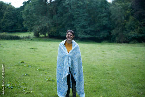 Mid adult woman standing in rural field wrapped in blanket, full length portrait