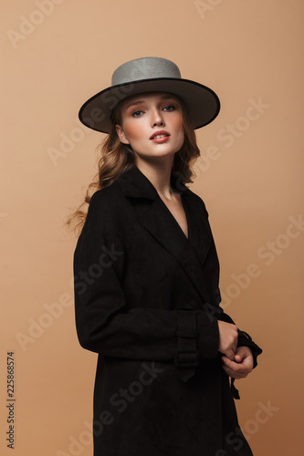 Fotografia  Young attractive woman with wavy hair in black coat and hat thoughtfully looking