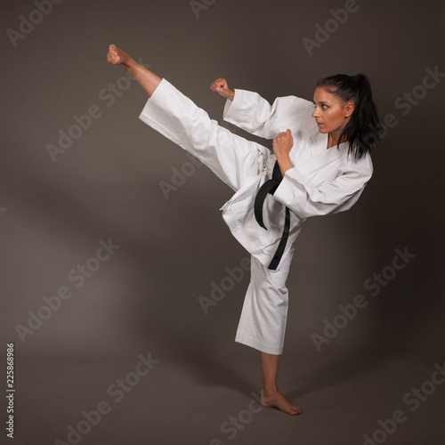 Photo  Woman in white  kimono kicks high in the air -  a karate  martial art girl