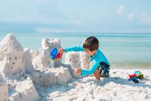 Boy Building Sandcastle On Beach