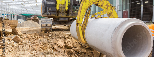 Leinwand Poster construction site excavator with a concrete pipe