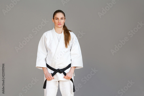 Garden Poster Martial arts Beautiful athletic young woman in white kimono standing and holding black belt and looking at camera with serious face. Japanese martial arts concept. Indoor, studio shot, isolated on grey background