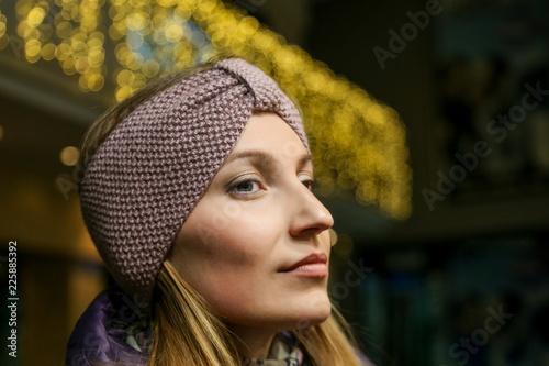 Portrait of young pretty woman in beautiful knitted woolen headband outdoors at cold autumn day Fototapeta