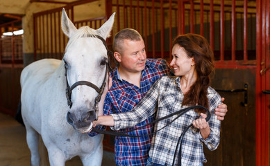 Mature smiling couple of farmers standing  with white horse at  stabling