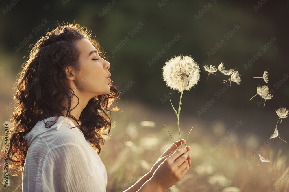 Fototapety, obrazy: Beautiful Young Woman sitting on the field in green grass and blowing dandelion. Outdoors. Enjoy Nature. Healthy Smiling Girl on summer lawn. Allergy free concept. Gorgeous slim mixed race Caucasian