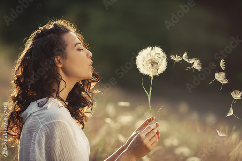 Tela Beautiful Young Woman sitting on the field in green grass and blowing dandelion