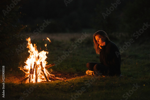 Fotografía Lonely young woman sitting and getting warm near the bonfire in the night forest