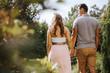 canvas print picture Rückansicht von schöner schwangeren Frau und ihrem Partner, welche Hand in Hand durch den Park laufen