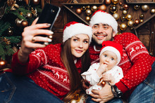 Portrait Of Beautiful Young Family In Red Christmas Sweaters And Santa Hats Making Self-portrait With Cute Baby Over Mobile Phone.