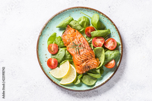 Photo Baked salmon fish fillet with fresh salad top view.