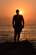 Silhouette of man on the sunset sea and sky