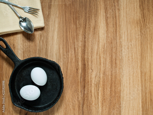 On a wooden background are a towel, spoon, fork, cast-iron pan, chicken eggs.
