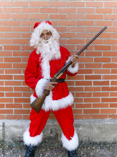 Fotografía  santa claus armed with shotgun