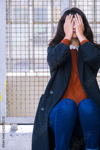 Young woman sitting near fence