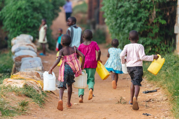 children carrying water cans in Uganda, Africa