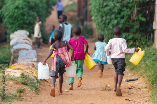 Foto op Canvas Afrika children carrying water cans in Uganda, Africa