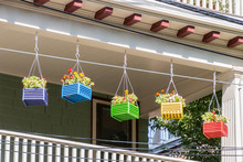 5 Small Multi-colored Square Wooden Planters With Blooming Flowers Hang From The Outer Edge Of A Second Story Porch. A Bannister Is In Lower Part Of The Picture. The Facade Is At The Top.