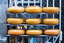 Nine Round Gouda Cheeses Stacked Outside A Cheese Factory Store In Amsterdam, Netherlands.