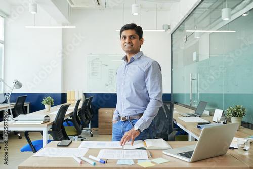 Obraz na plátně Portrait of happy Indian UX designer standing in modern office