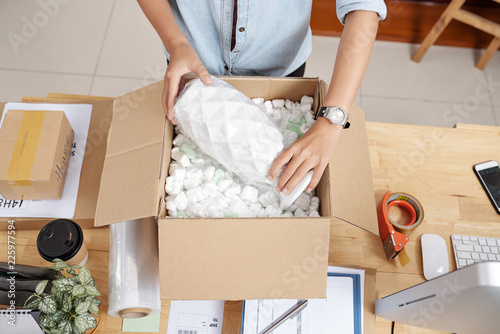 Fototapeta Small business owner packing vase to send it to customer, view from above obraz