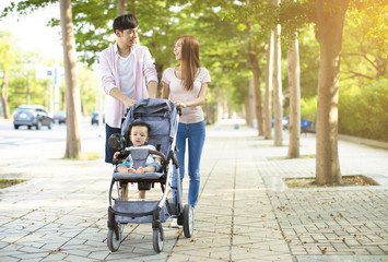 Fototapeta happy family with baby carriage walking in the park