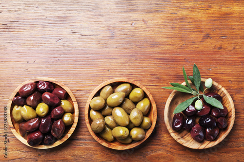 Set from olives in wooden bowls decorated with olive tree branch top view.