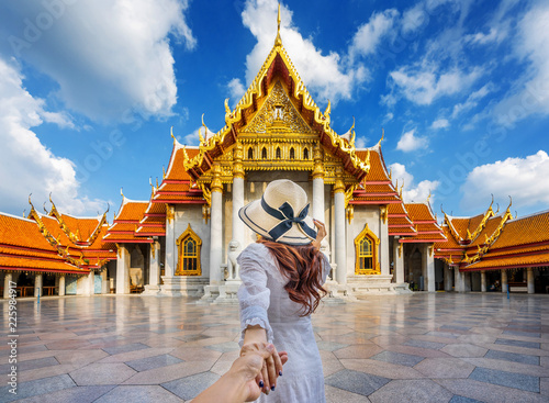 In de dag Bangkok Women tourists holding man's hand and leading him to Wat Benchamabophit or the Marble Temple in Bangkok, Thailand.