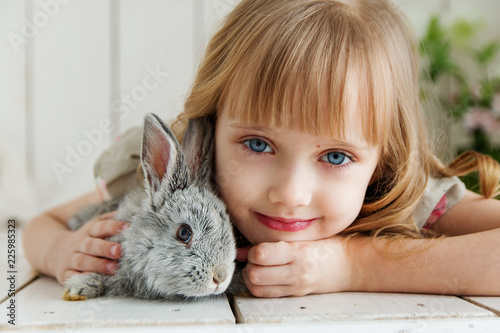 Fototapeta Cute girl hugging with rabbit while lying on the floor at home