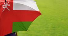 Oman Flag Umbrella. Close Up Of Printed Umbrella Over Green Grass Lawn / Field. Rainy Weather Forecast Concept.