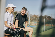Happy Senior Man And Woman Talking While Sitting On Bench At Tennis Court