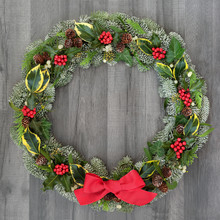 Christmas And Winter Wreath With Holly, Mistletoe, Ivy, Spruce Fir, Pine Cones And A Red Bow On Rustic Grey Wood  Background.
