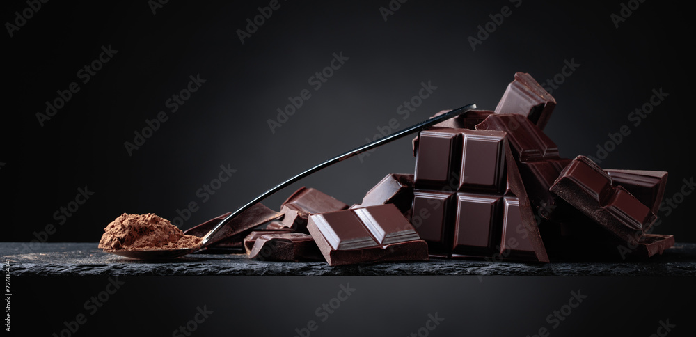 Fototapety, obrazy: Broken chocolate pieces and cocoa powder on black background.